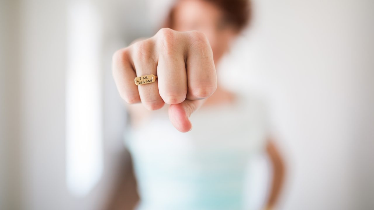 woman showing gold-colored ring
